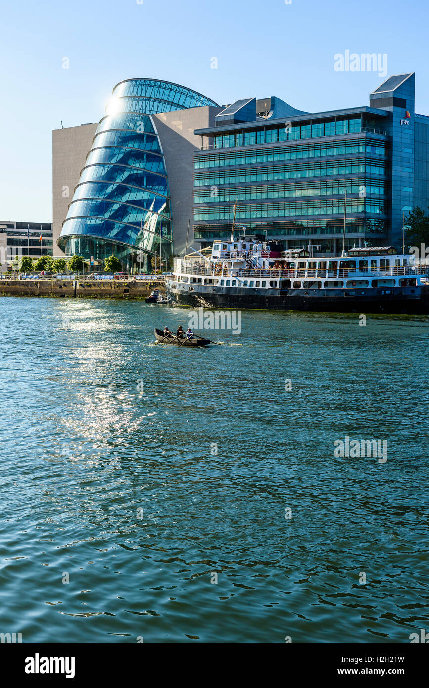 Dragon boat on River Liffey Dublin Ireland with Convention Centre Dublin, offices of pwc, and MV Cill Airne floating - Stock Image