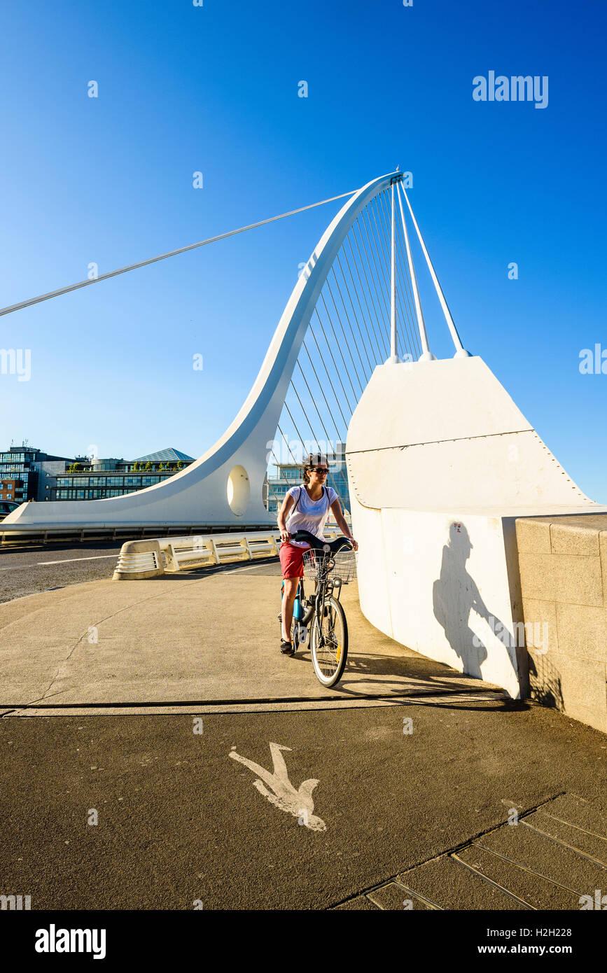 Cyclist at south end of Samuel Beckett Bridge over River Liffey Dublin Ireland Stock Photo