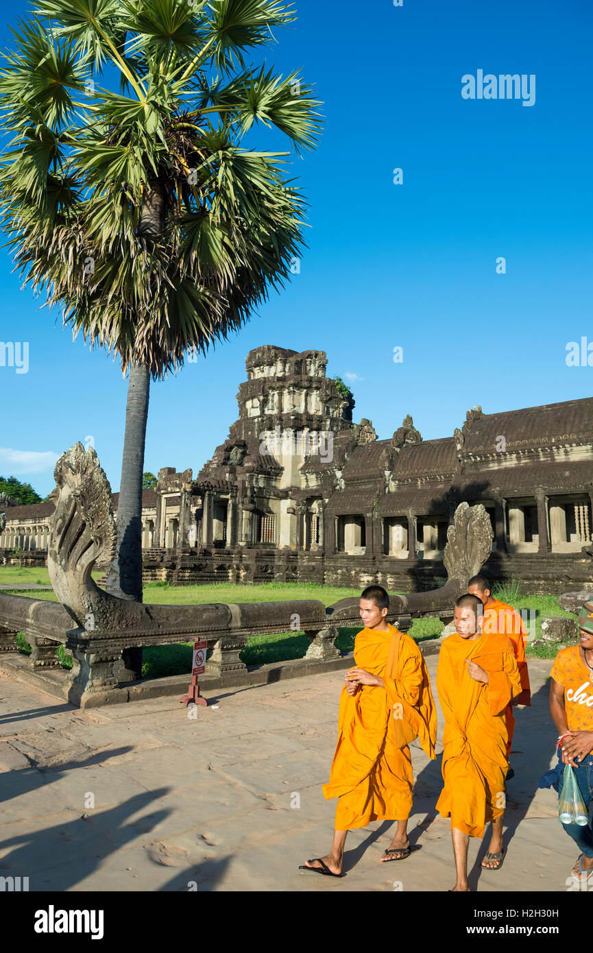 SIEM REAP, CAMBODIA - OCTOBER 30, 2014: Novice Buddhist monks in saffron orange robes pass in front of Angkor Wat. - Stock Image