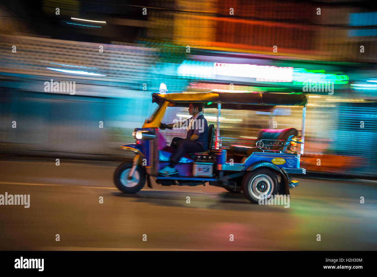 BANGKOK - NOVEMBER 18, 2014: A motorized tuktuk, the ubiquitous local transportation, drives at night looking for - Stock Image