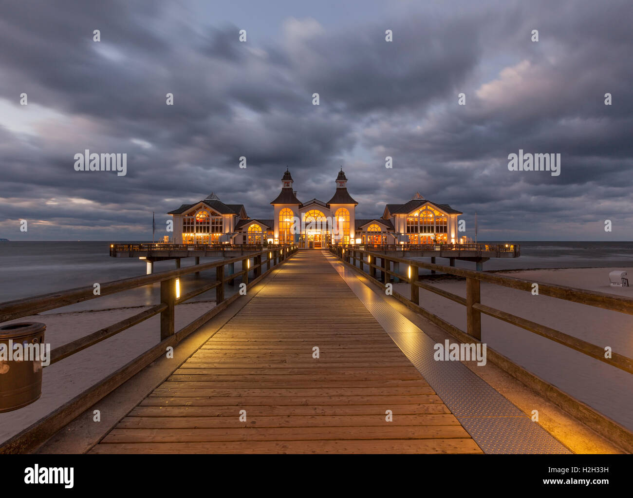 Illuminated historic pier at Ostseebad Sellin, Ruegen, Germany, at night, long exposure - Stock Image