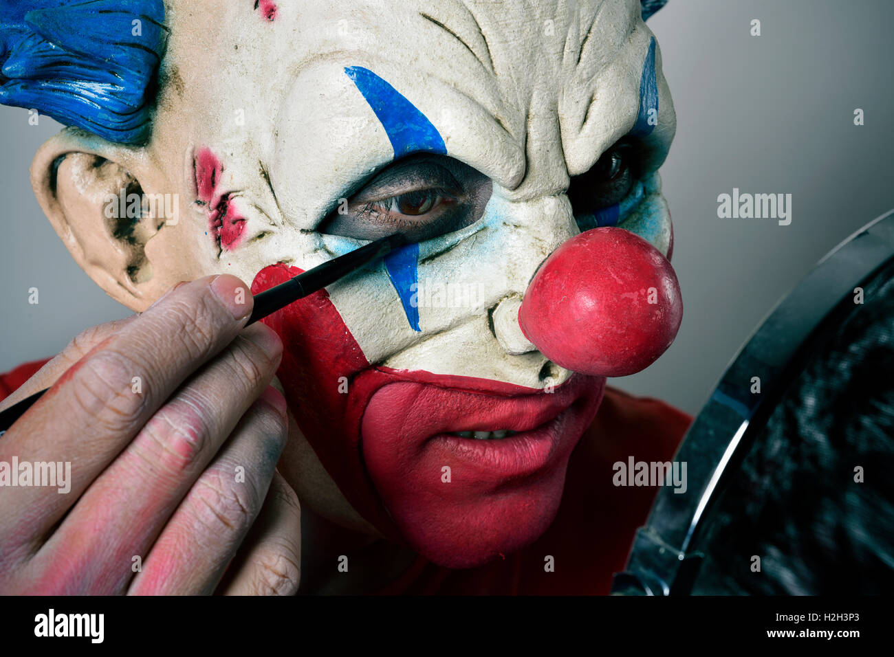 closeup of a young man making up himself as an evil clown, using a mirror - Stock Image