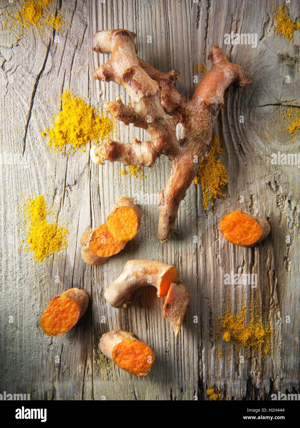 Fresh whole and cut turmeric or tumeric root (Curcuma longa) - Stock Image