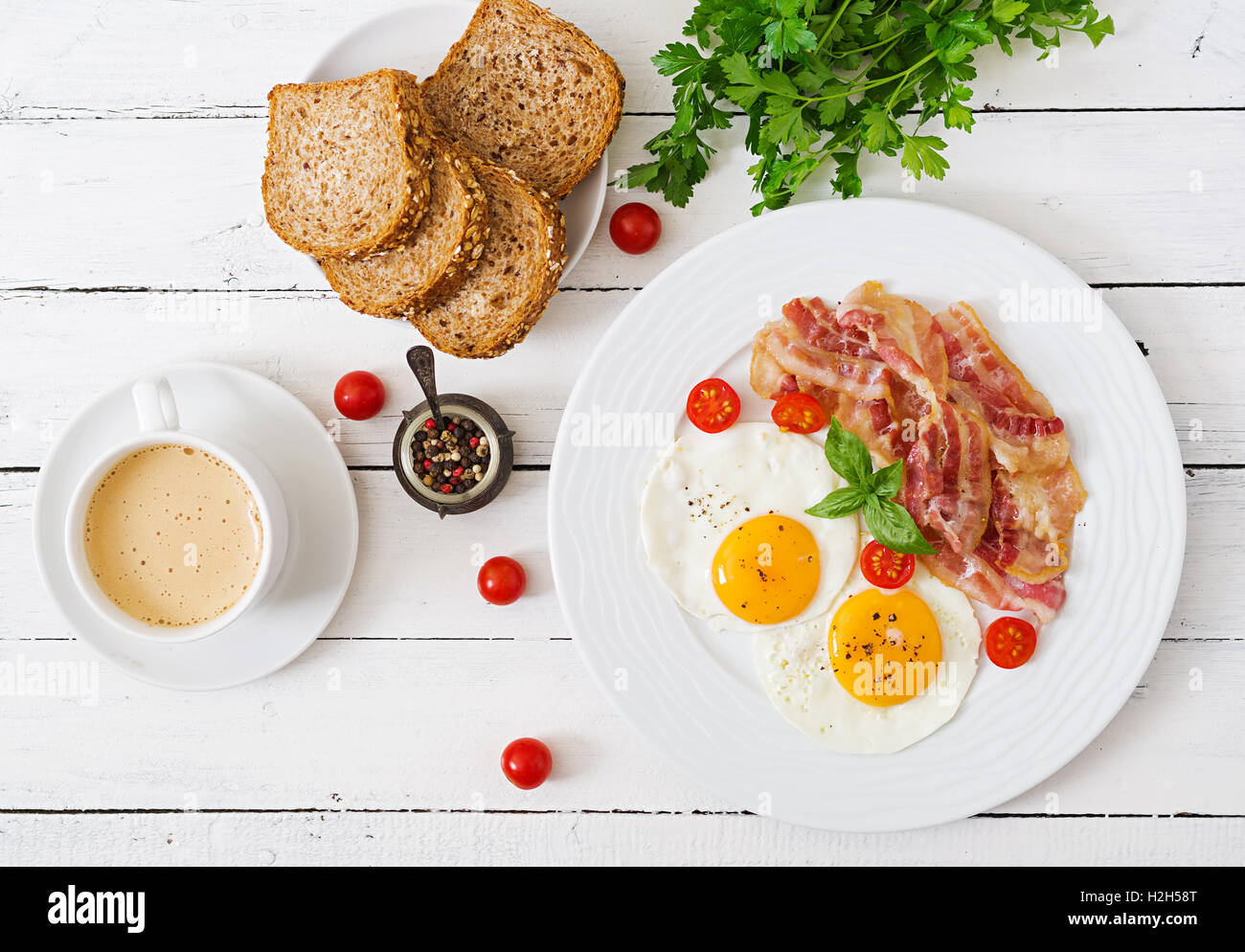 English breakfast - fried egg, tomatoes and bacon. Top view. - Stock Image