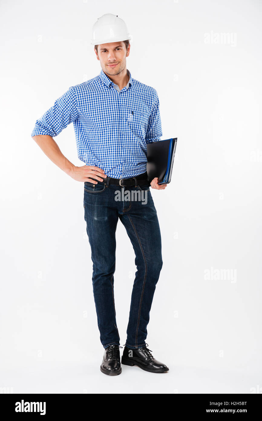 Confident young man builder in hard hat standing and holding folder - Stock Image