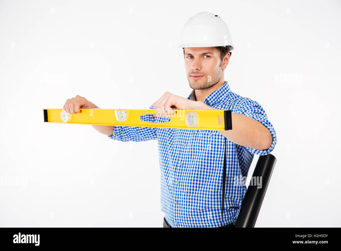 Serious young man building engineer in hard hat using spirit level - Stock Image