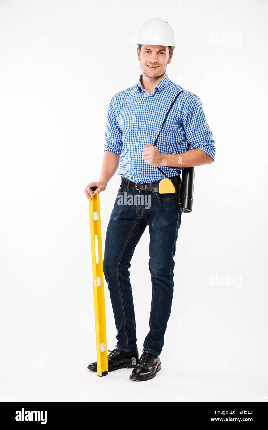 Cheerful young man builder in hard hat standing and holding spirit level - Stock Image
