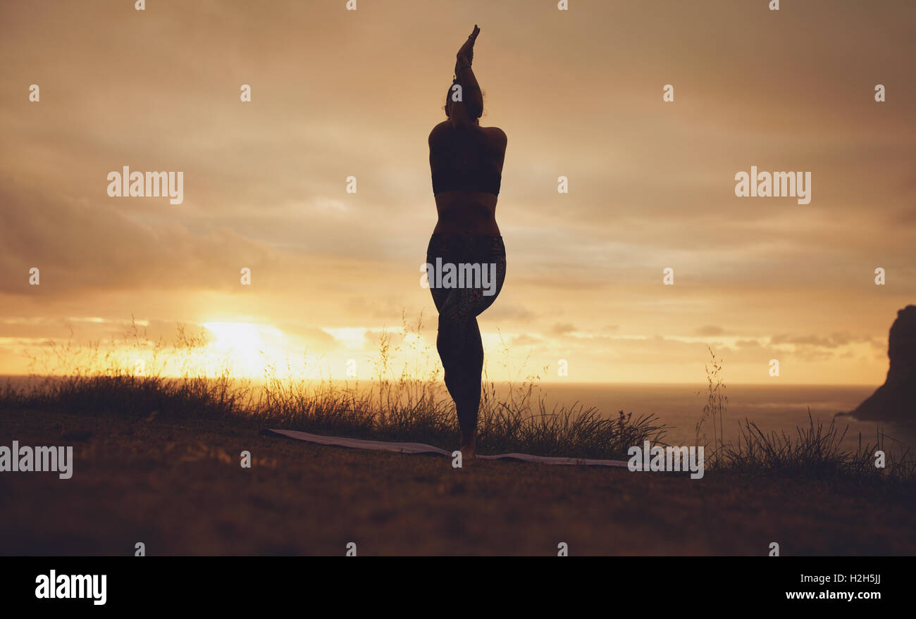 Silhouette of a woman practicing yoga, Garudasana, Eagle pose. Fitness female standing on mat doing yoga with her - Stock Image