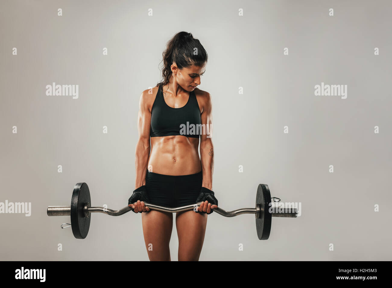Female athlete strengthening biceps with curved barbell over gray background with copy space - Stock Image