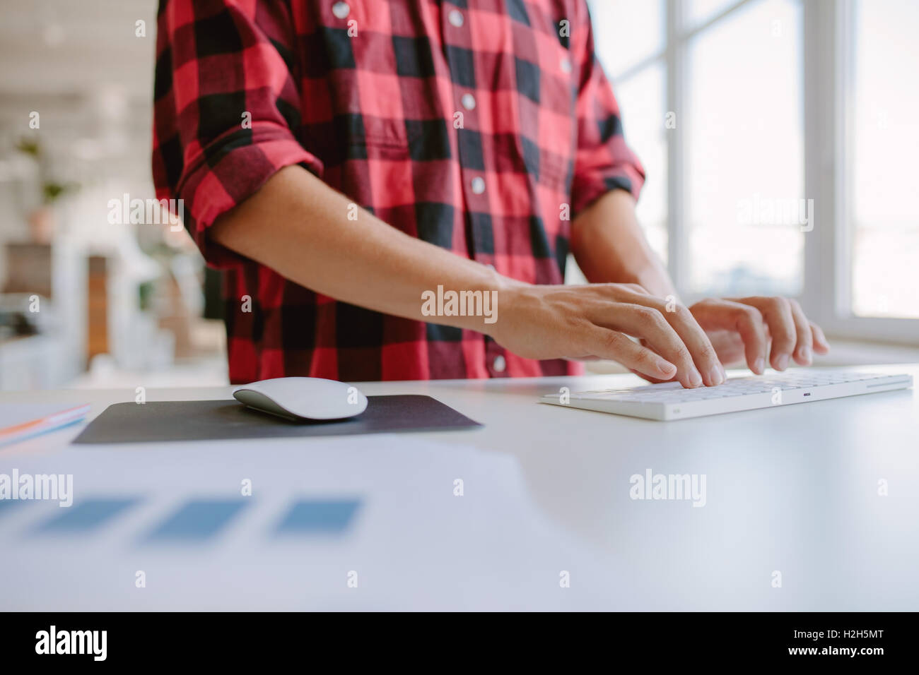 Close up of man hands typing on computer keyboard. Cropped shot businessman working on computer while standing at - Stock Image