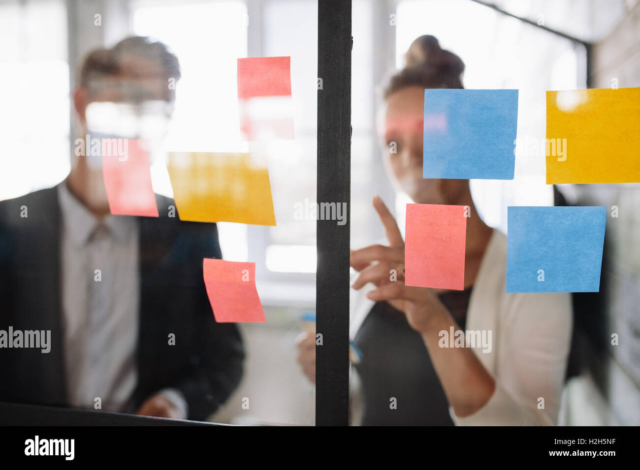 Two business colleagues working on project together. Business woman pointing at sticky note to male colleague on - Stock Image