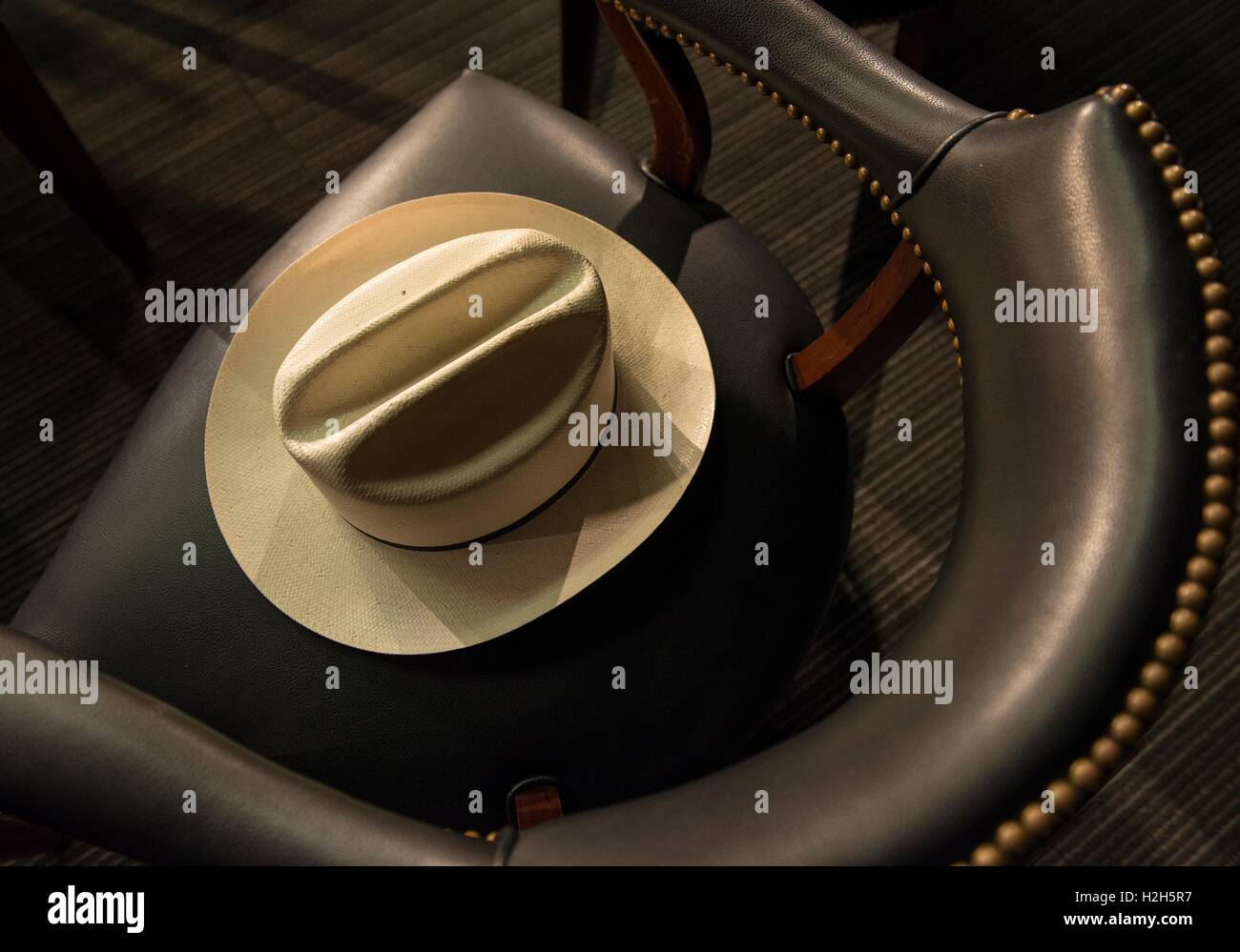 A ten-gallon cowboy hat sits in a leather arm chair during a special event between the Texas Tribune and the LBJ - Stock Image