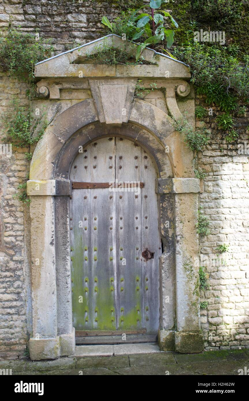 Studded rustic wooden door in stone wall with decorative surround and foliage Stock Photo
