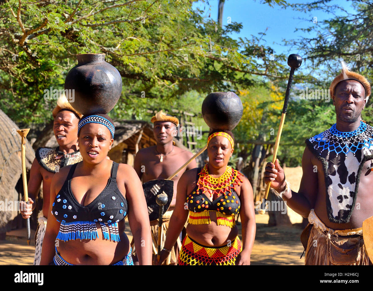 Zulu troupe with girl performers carrying  water-bowls during a Zulu experience performance at the Shakaland Cultural - Stock Image