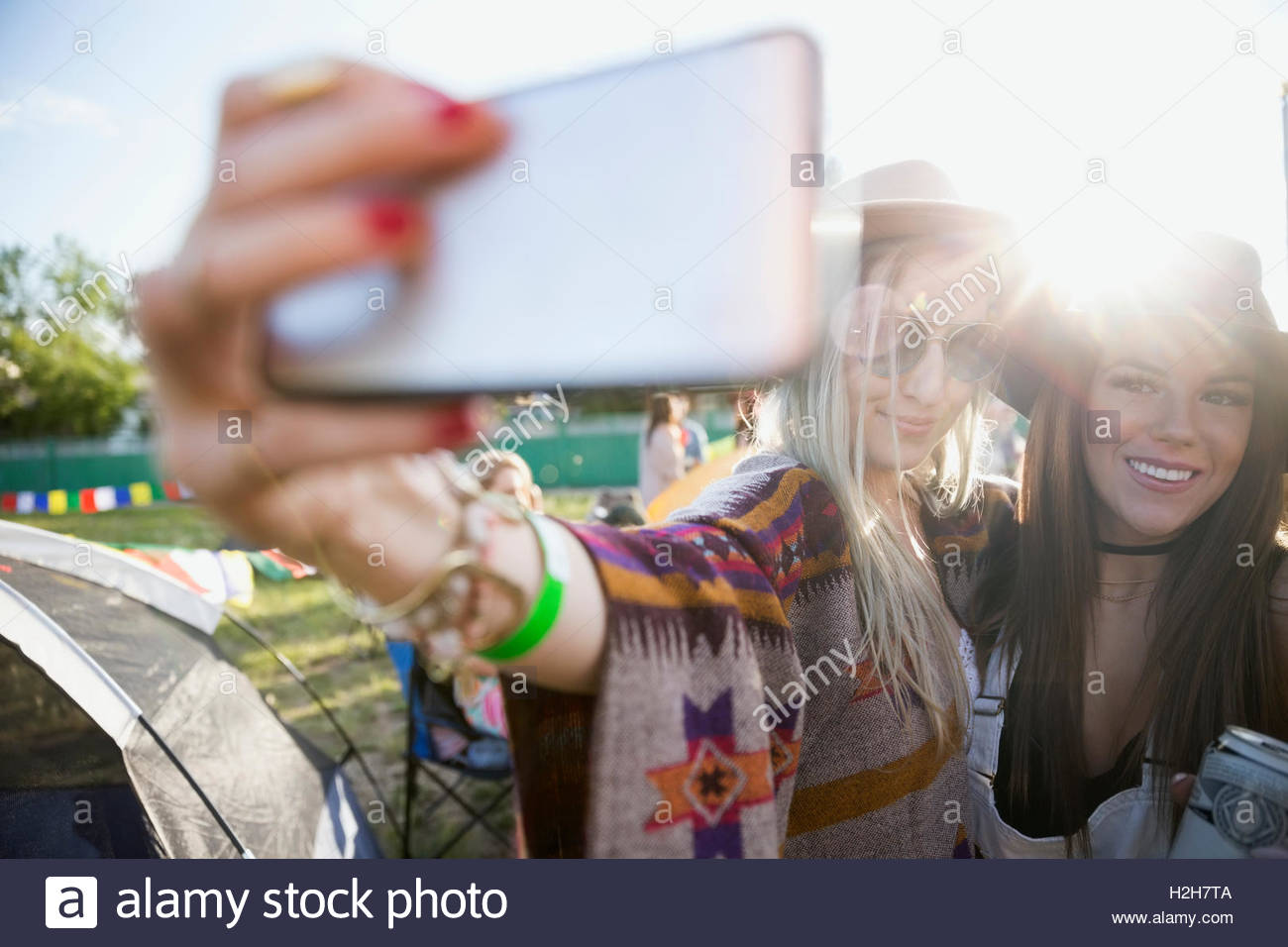 Young women taking selfie at summer music festival campsite - Stock Image