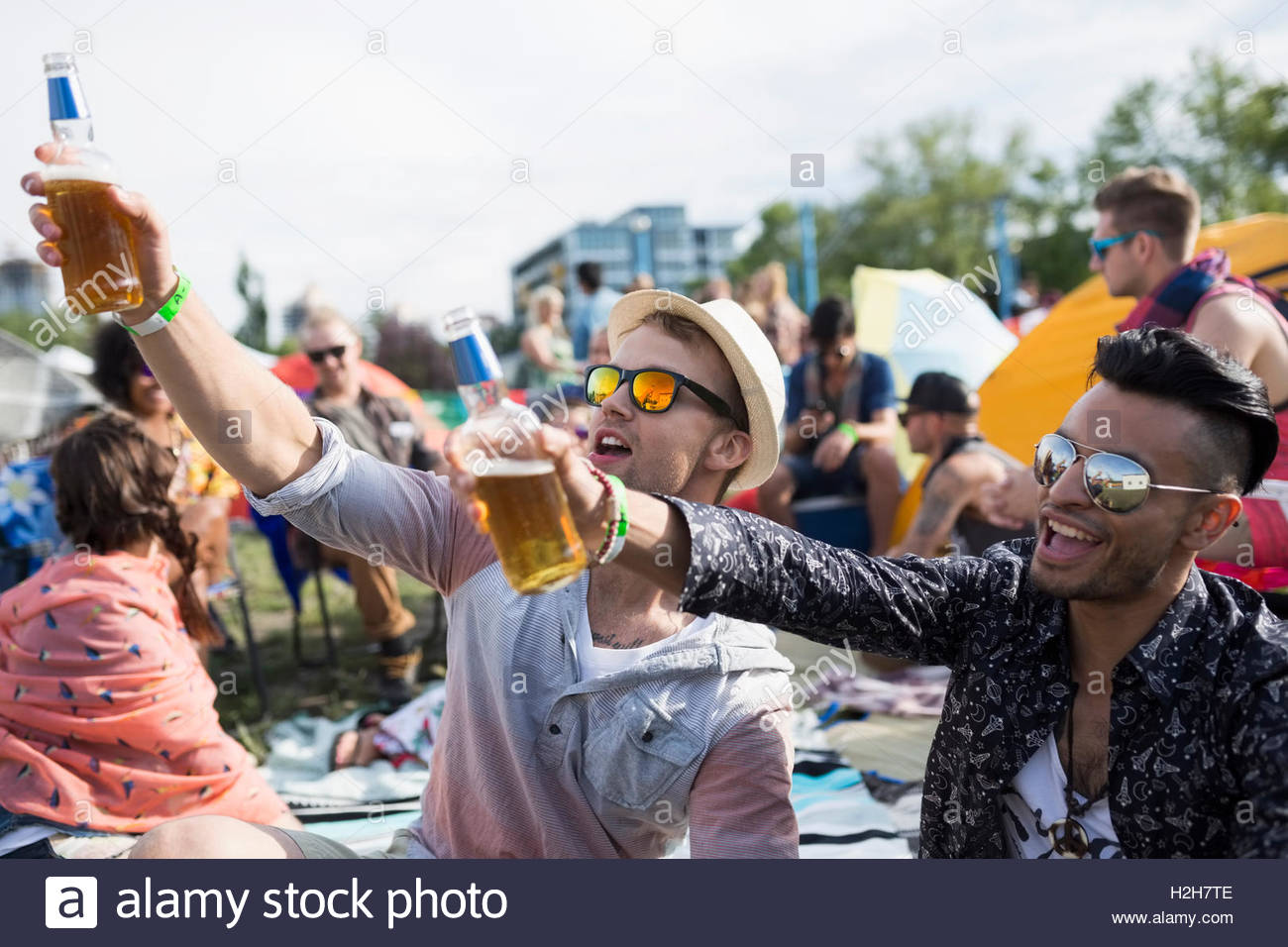 Young men drinking beer cheering at summer music festival campsite - Stock Image