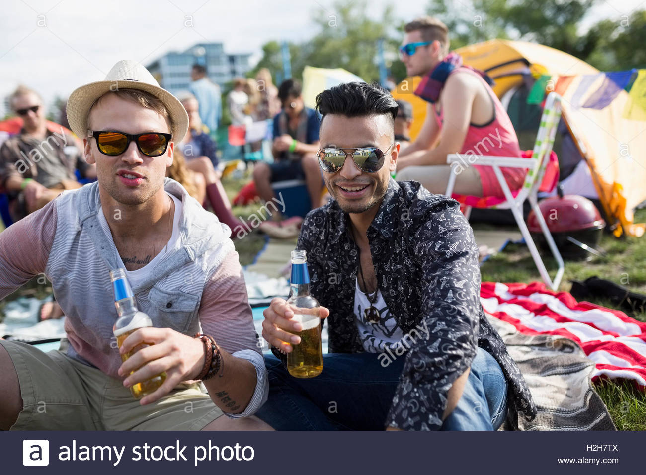 Portrait young men drinking beer at summer music festival campsite - Stock Image