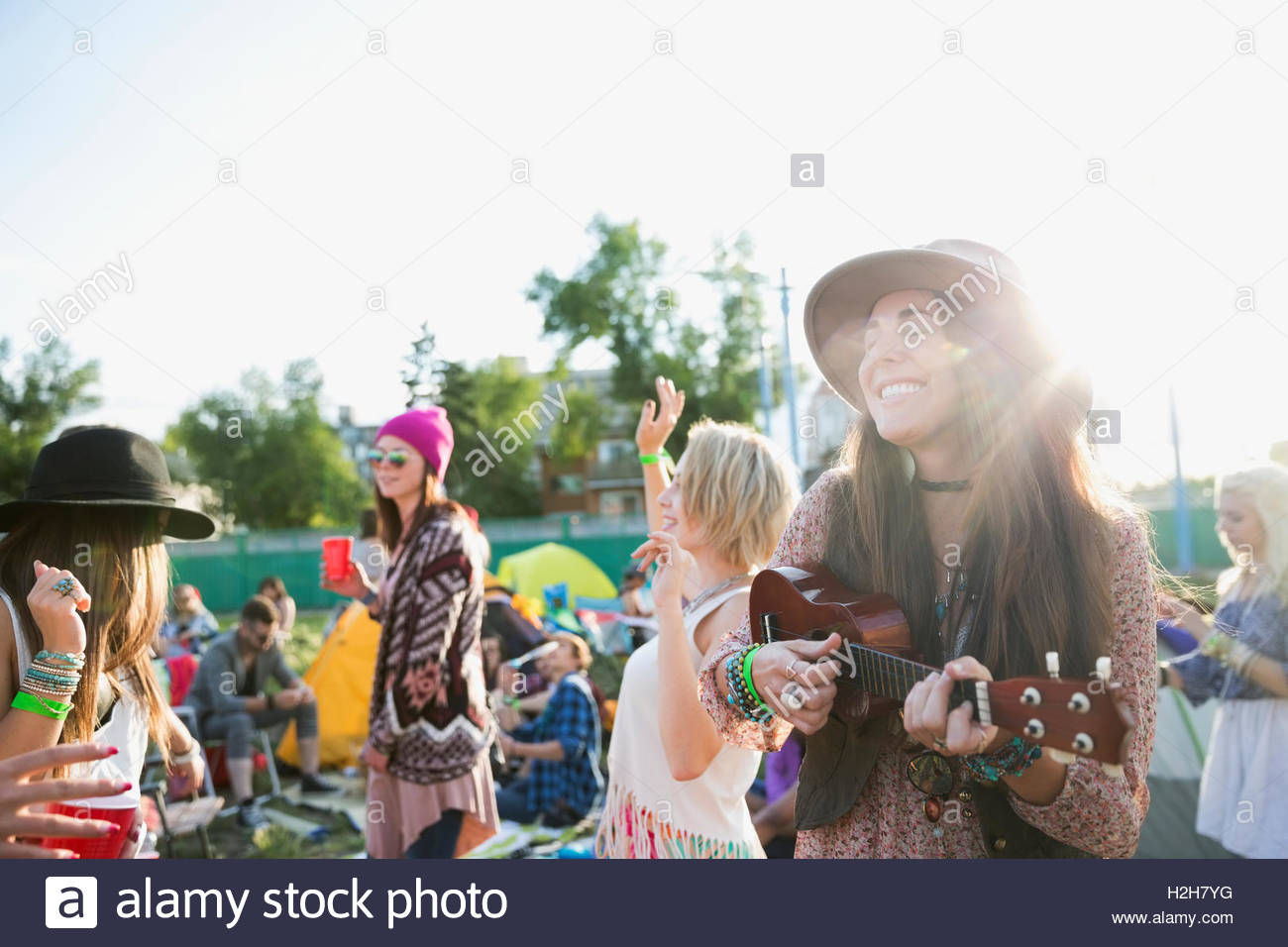 Smiling young woman playing ukulele at summer music festival campsite - Stock Image