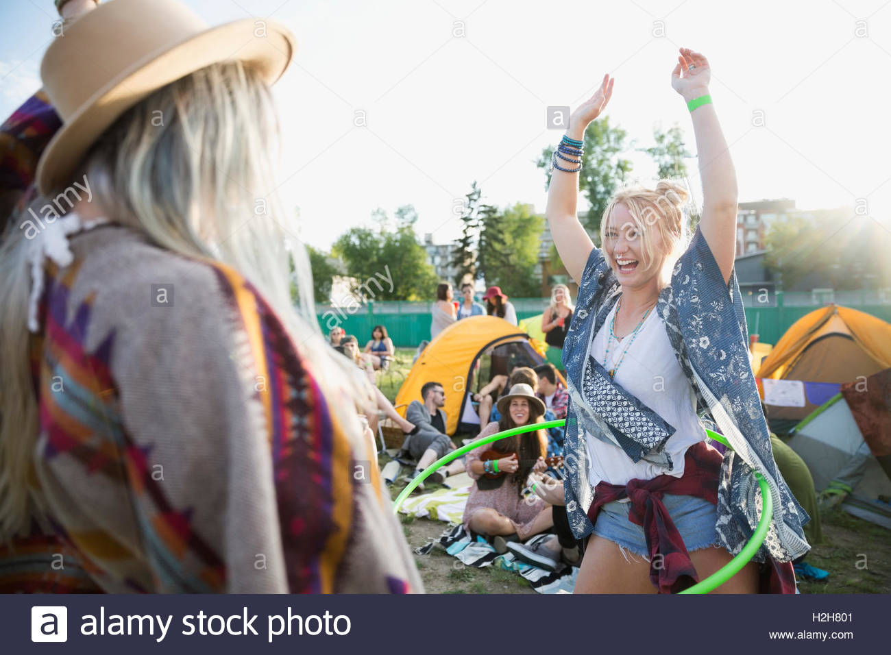 Playful young woman spinning with plastic hoop at summer music festival campsite - Stock Image