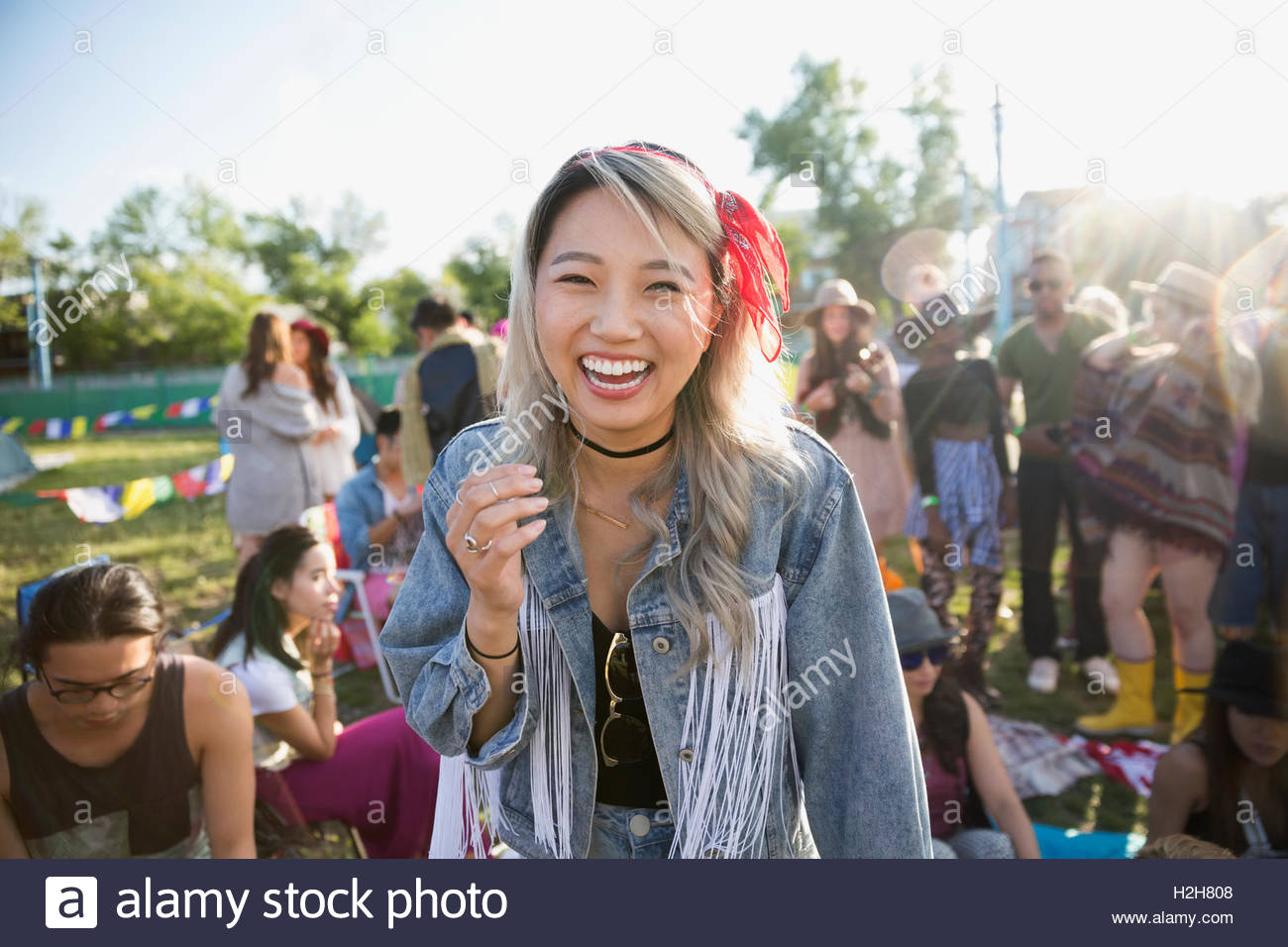 Portrait laughing young woman at summer music festival campsite - Stock Image