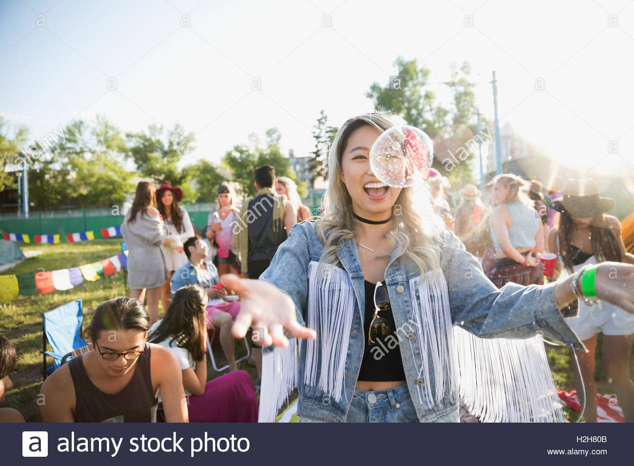 Playful young woman with bubbles at summer music festival campsite - Stock Image