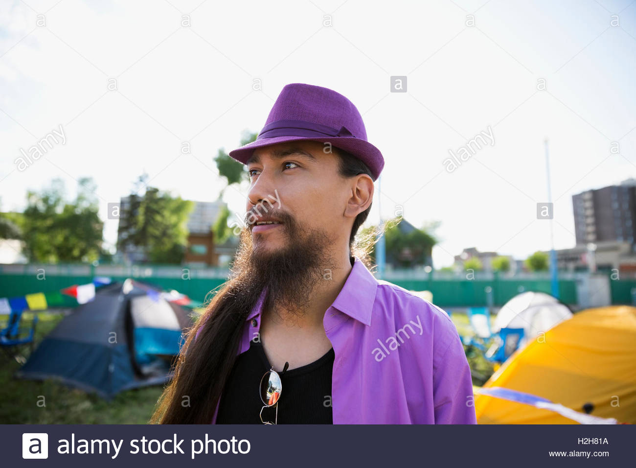 Young man with long hair and beard wearing purple hat looking away at summer music festival campsite - Stock Image