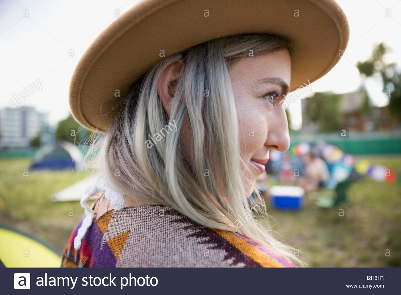 Close up portrait young woman with chalk dyed hair wearing hat looking away at summer music festival campsite - Stock Image