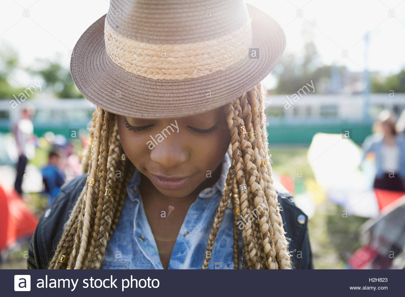 Close up portrait young woman with blonde braids wearing hat looking down at summer music festival campsite - Stock Image