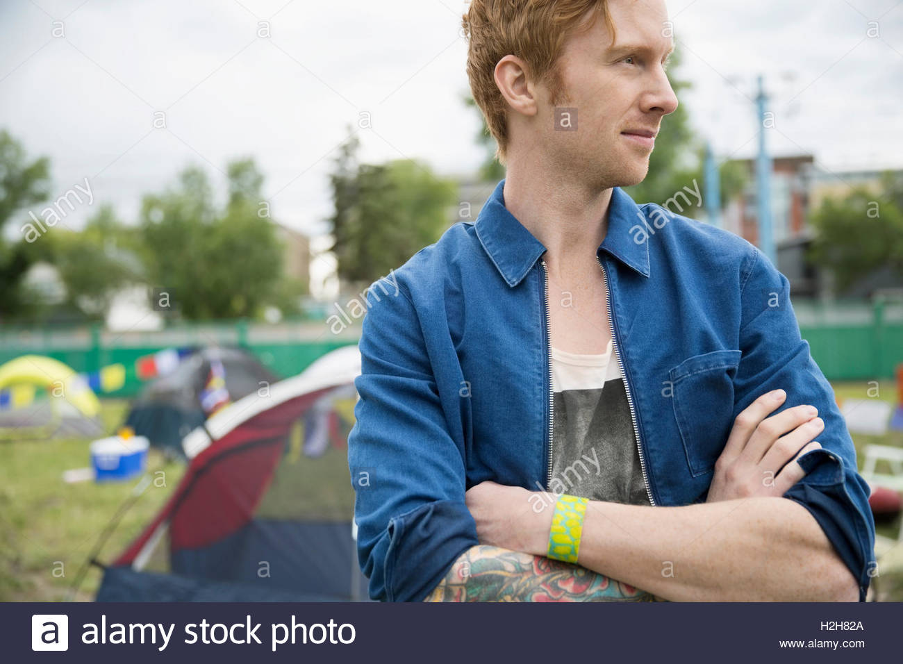 Portrait pensive young man with red hair looking away at summer music festival campsite - Stock Image