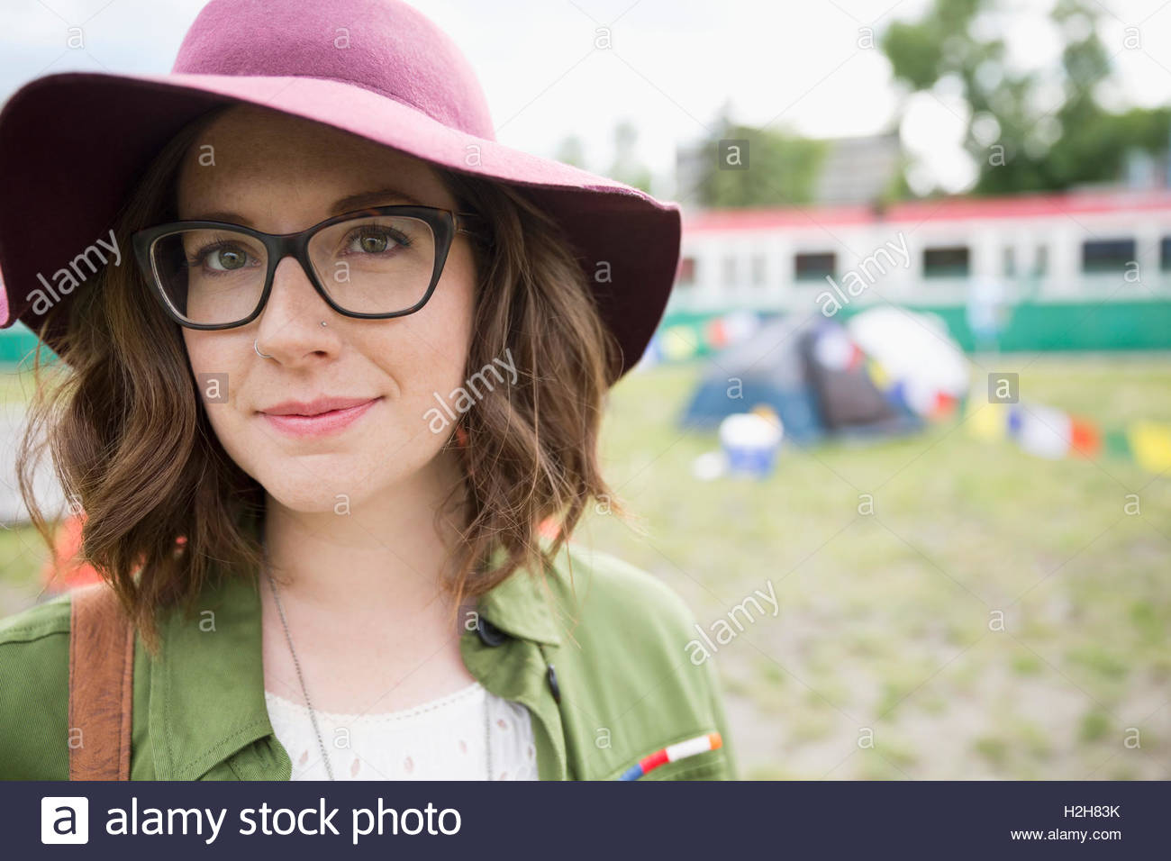 4cf110c27e Portrait smiling young brunette woman wearing floppy hat and eyeglasses at  summer music festival campsite -