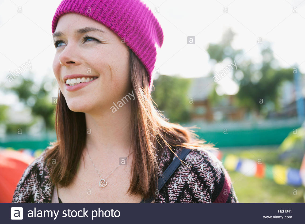 Portrait smiling brunette woman wearing stocking cap looking away at summer music festival campsite - Stock Image