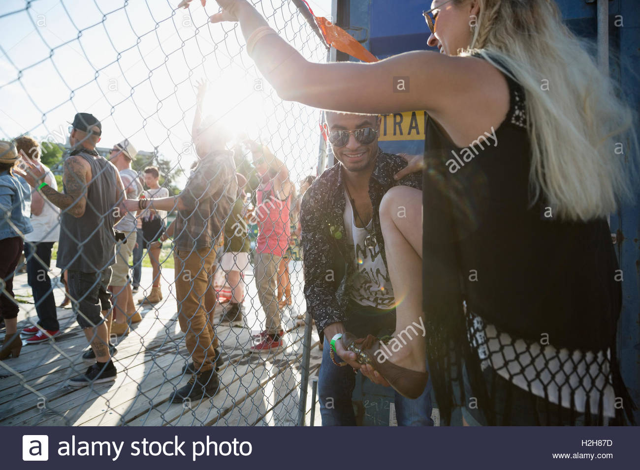 Young man helping woman climb fence at summer music festival - Stock Image