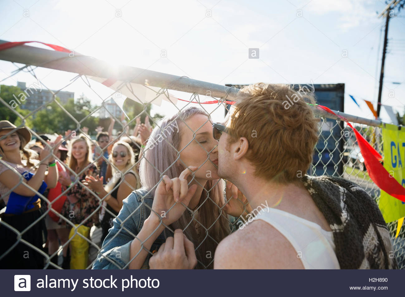 Young couple kissing through chainlink fence at summer music concert - Stock Image