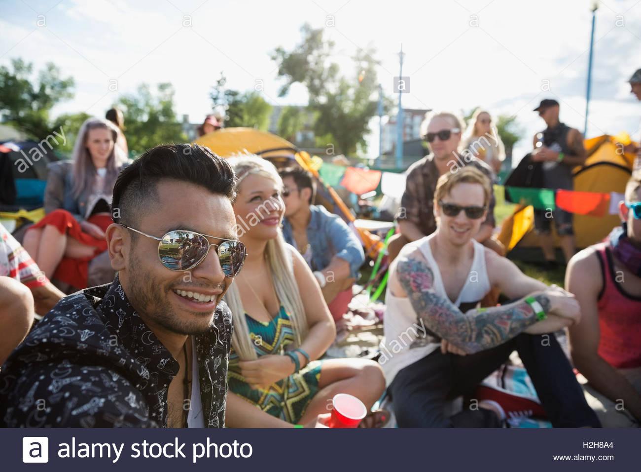 Portrait confident young men enjoying summer music festival - Stock Image