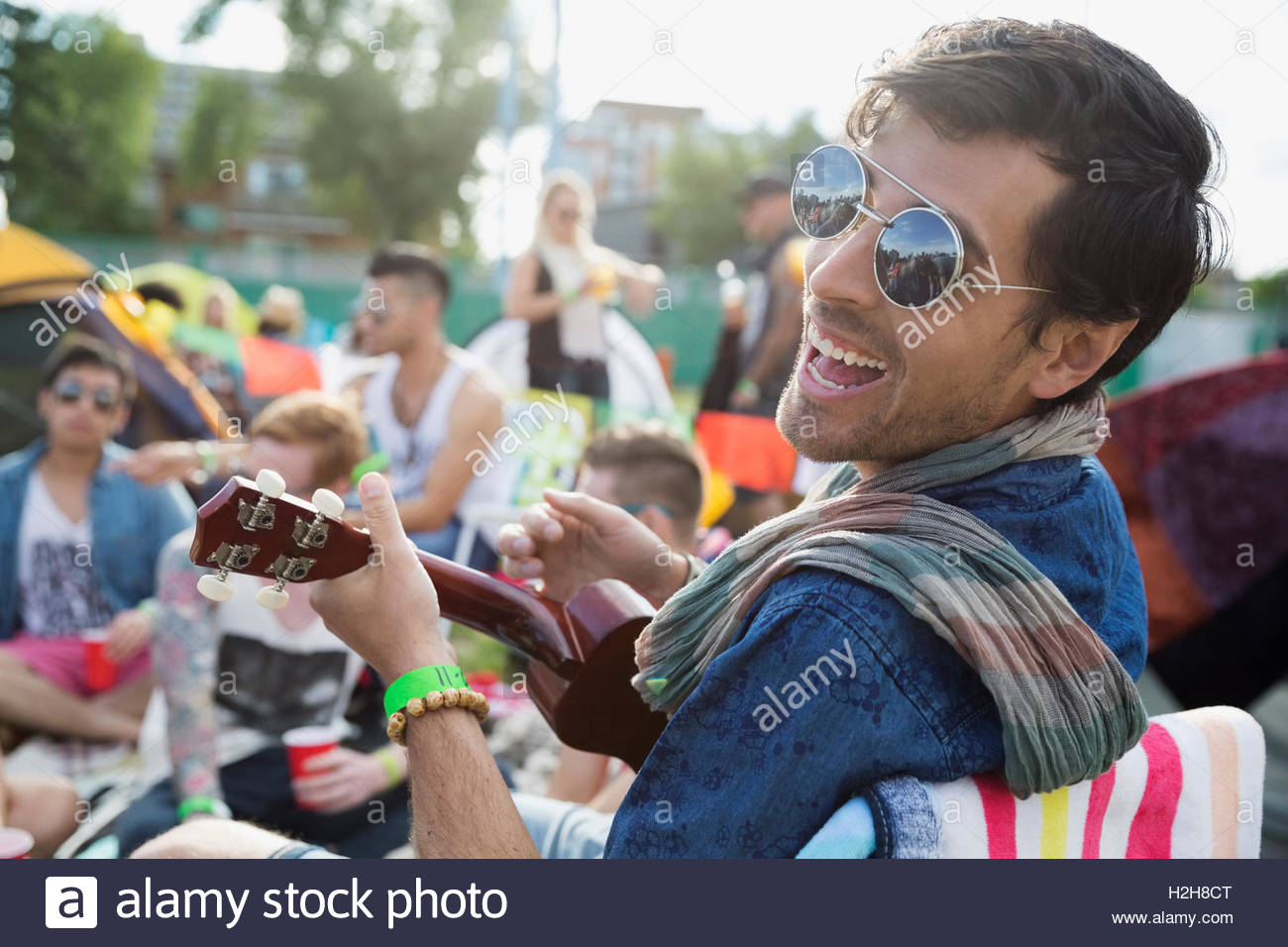 Portrait enthusiastic young man playing ukulele at summer music festival campsite - Stock Image