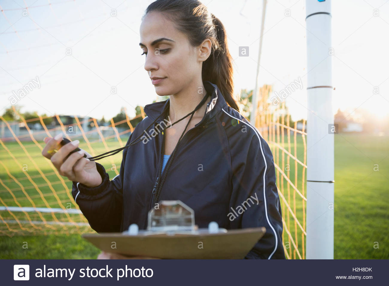Soccer coach with stopwatch and clipboard at goal net - Stock Image