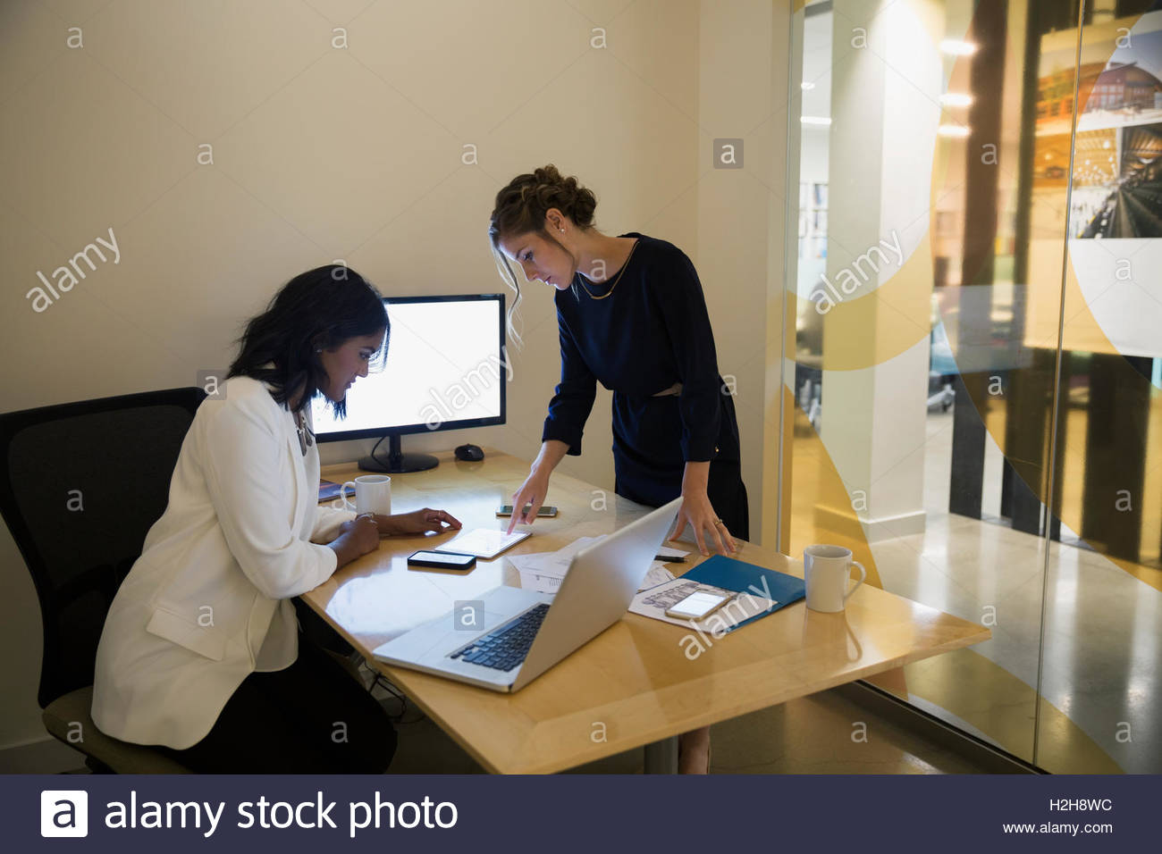 Businesswomen using digital tablet in conference room Stock Photo