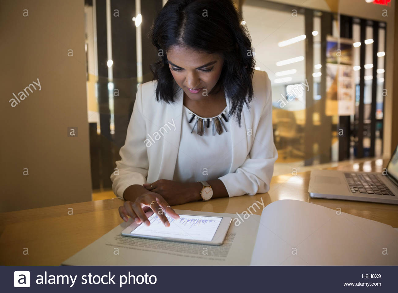Businesswoman using digital tablet in conference room - Stock Image