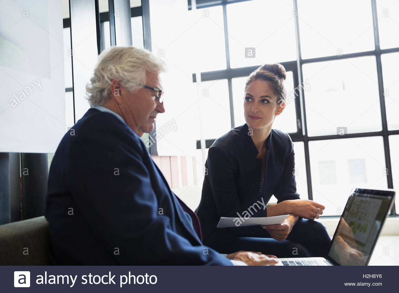 Business people with paperwork working at laptop in office - Stock Image