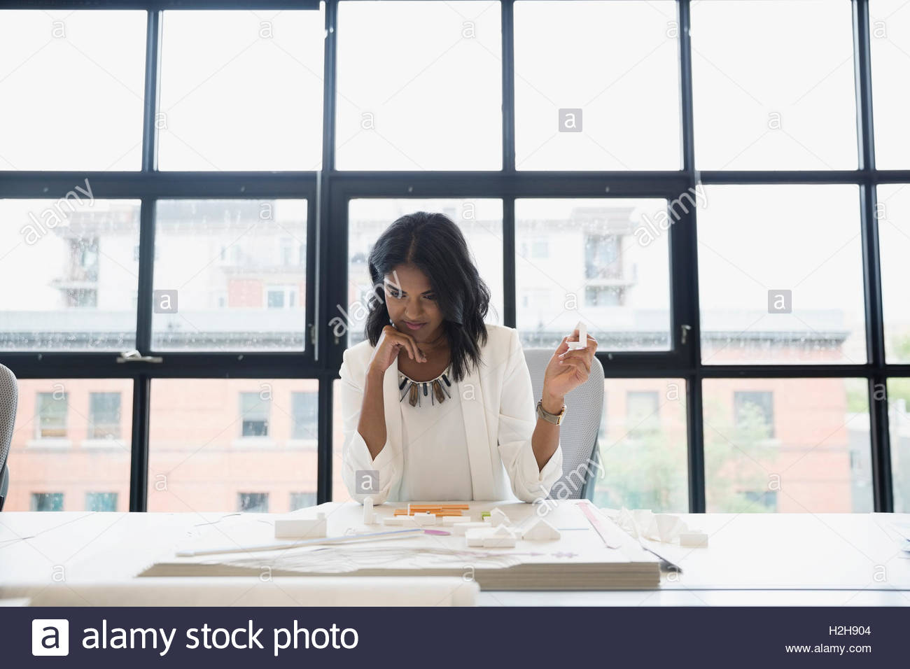 Female architect reviewing model at table in office - Stock Image