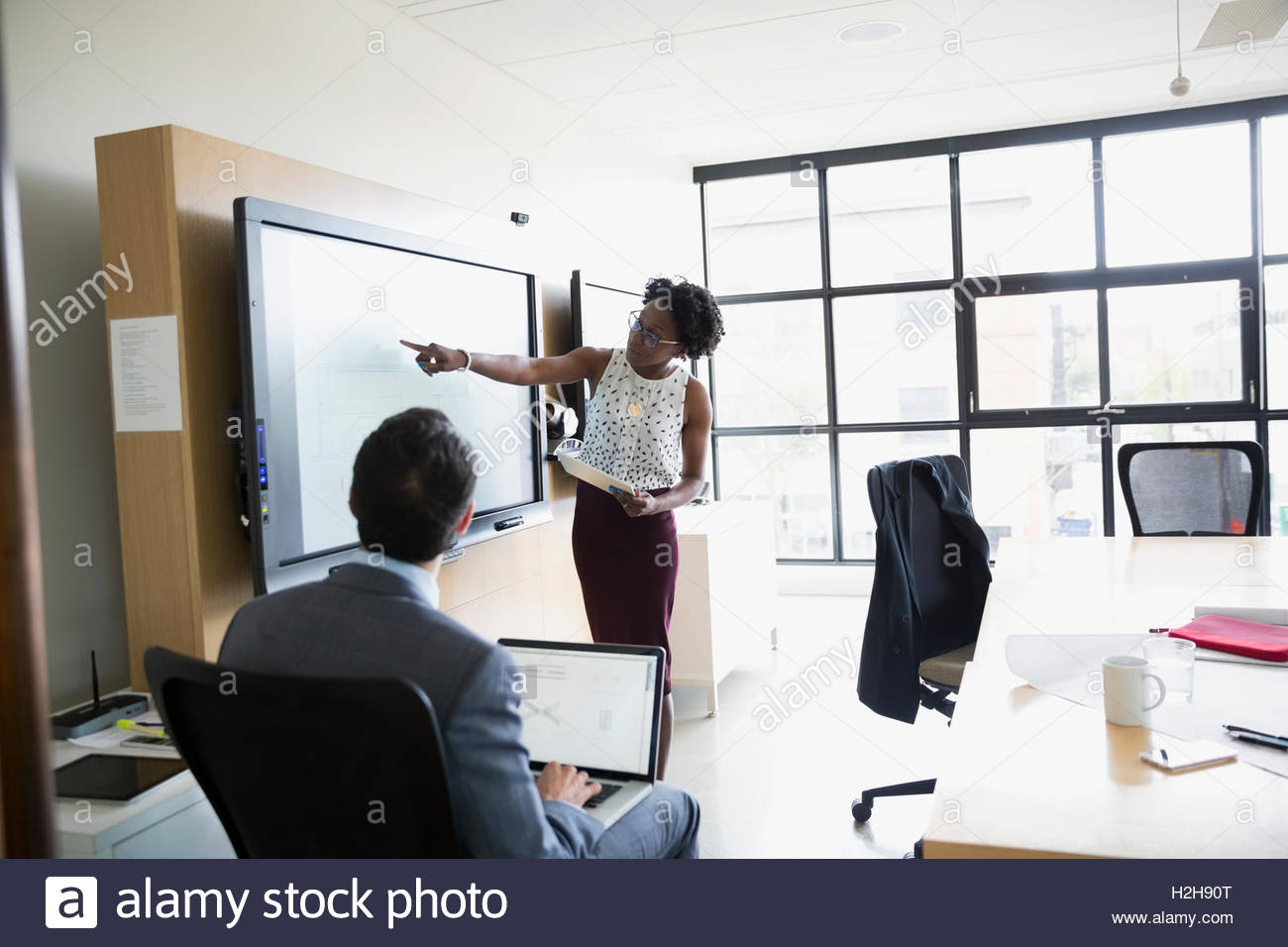 Business people using television in conference room meeting - Stock Image
