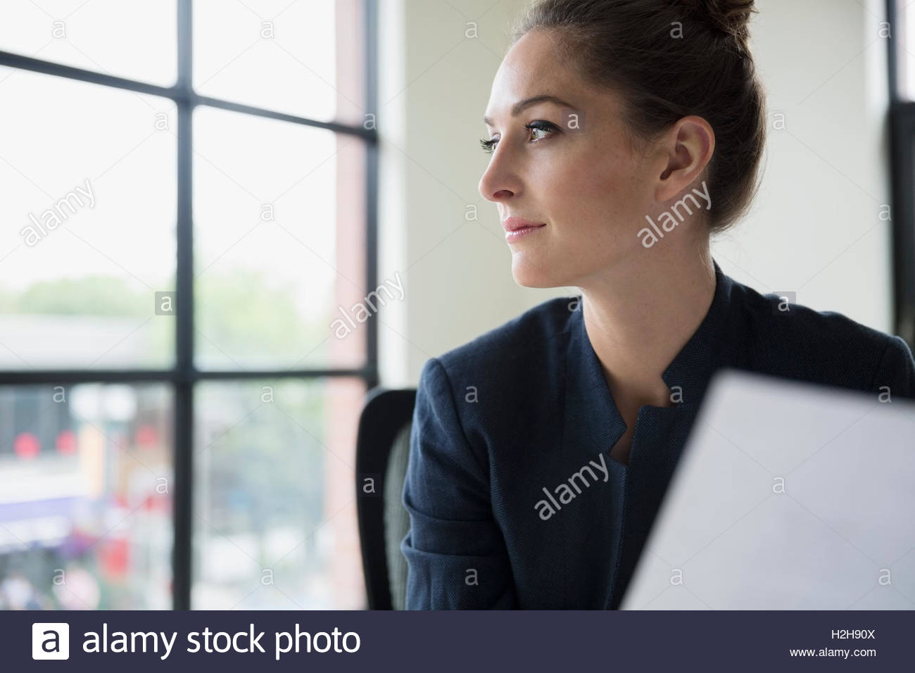 Pensive businesswoman with paperwork looking out office window - Stock Image