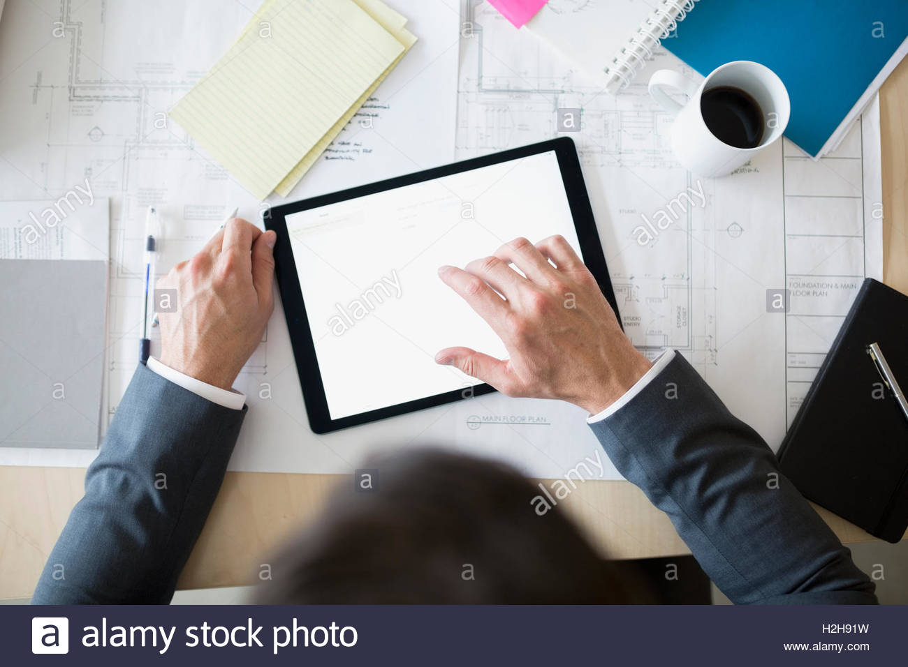 Overhead view architect using digital tablet - Stock Image