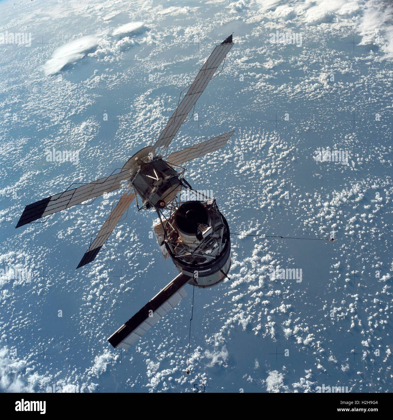 An aerial view of the NASA Skylab space station cluster above clouds against the Earth background while in Earth - Stock Image