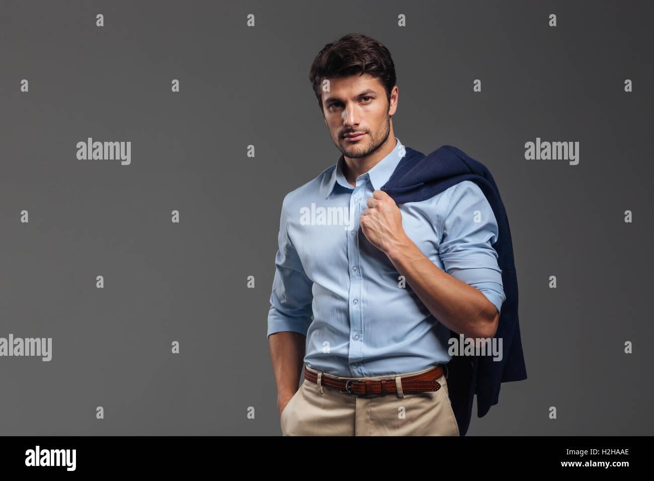 Handsome businessman holding his jacket over shoulder on gray background - Stock Image