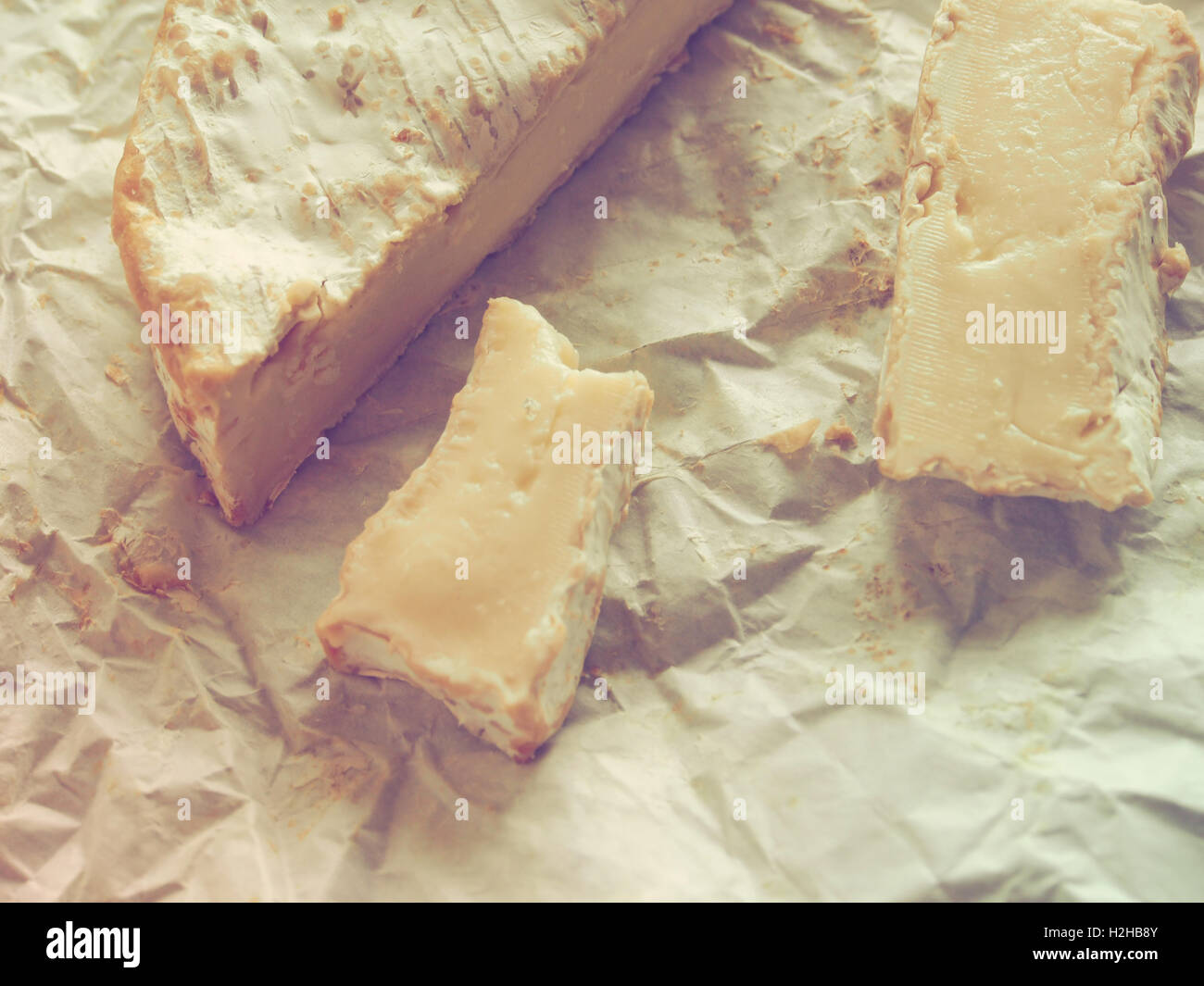 Camembert on crumpled wrapping paper. Grunge style. - Stock Image