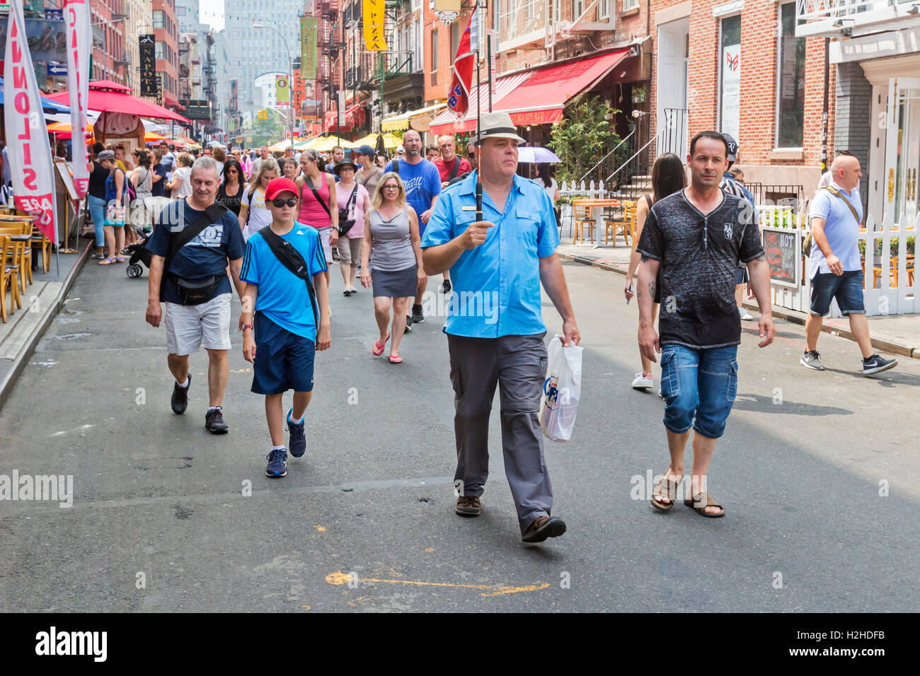 A tour guide travels with tourists walking in Little Italy, New York City. - Stock Image