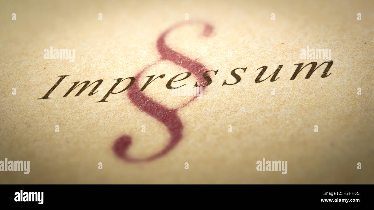 Word Impressum printed on a paper texture with blur effect and silcrow symbol - Stock Image