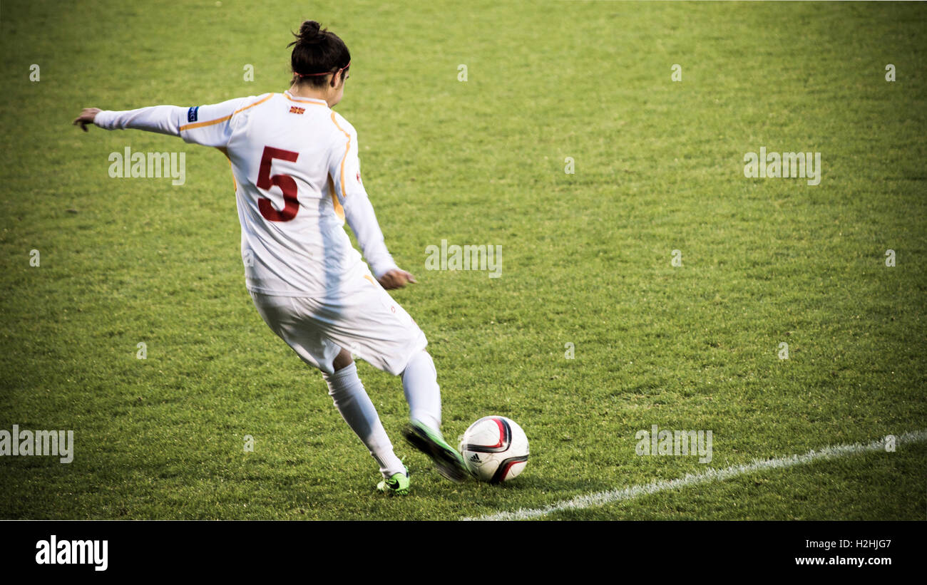 Female footballer kicking ball mid-game - Stock Image