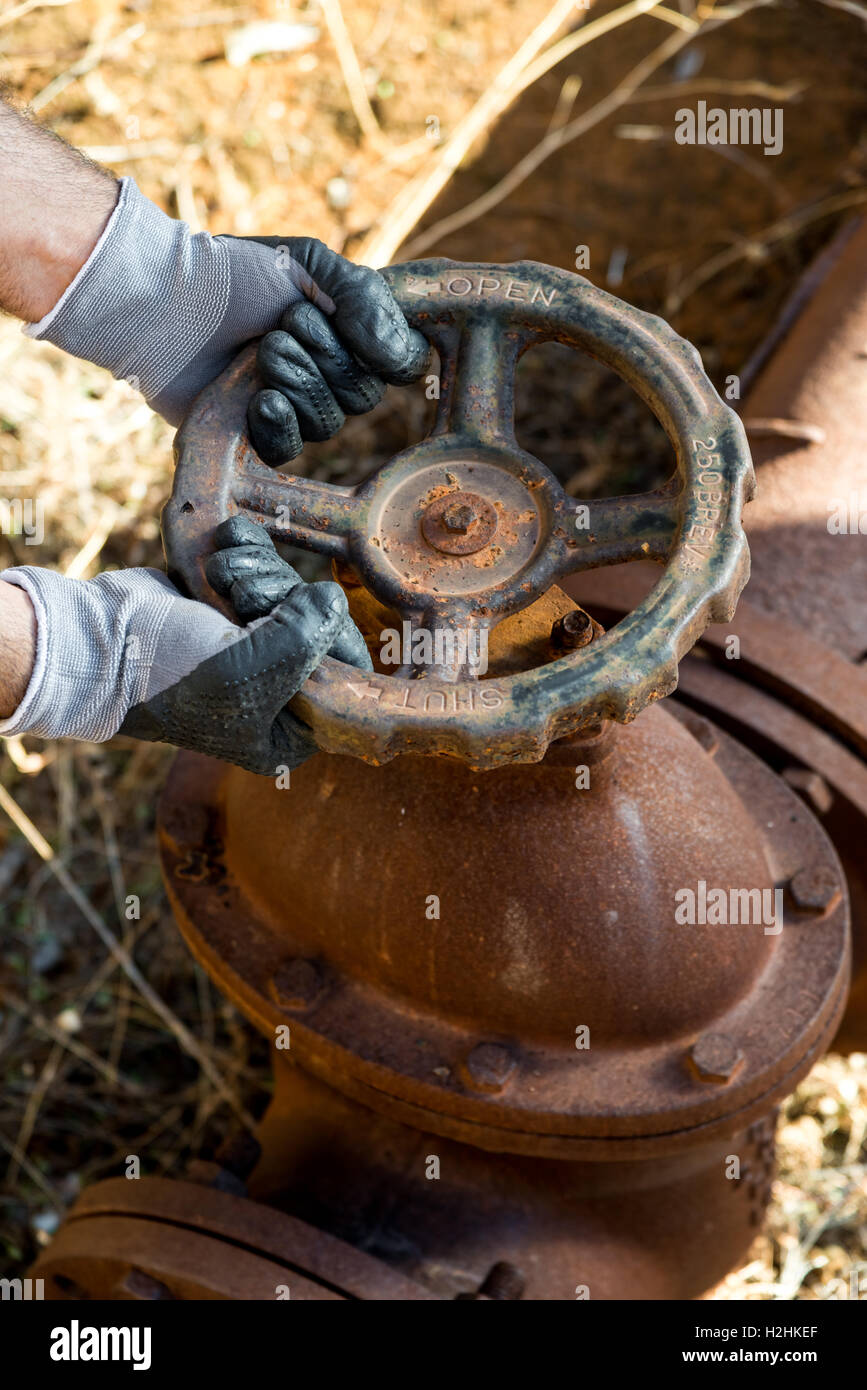Hands with Work Gloves Clutching a Pipe Valve of a very old and Rusty Water line - Stock Image
